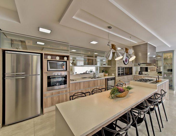 Cozinha planejada com ilha grande e armários de madeira.