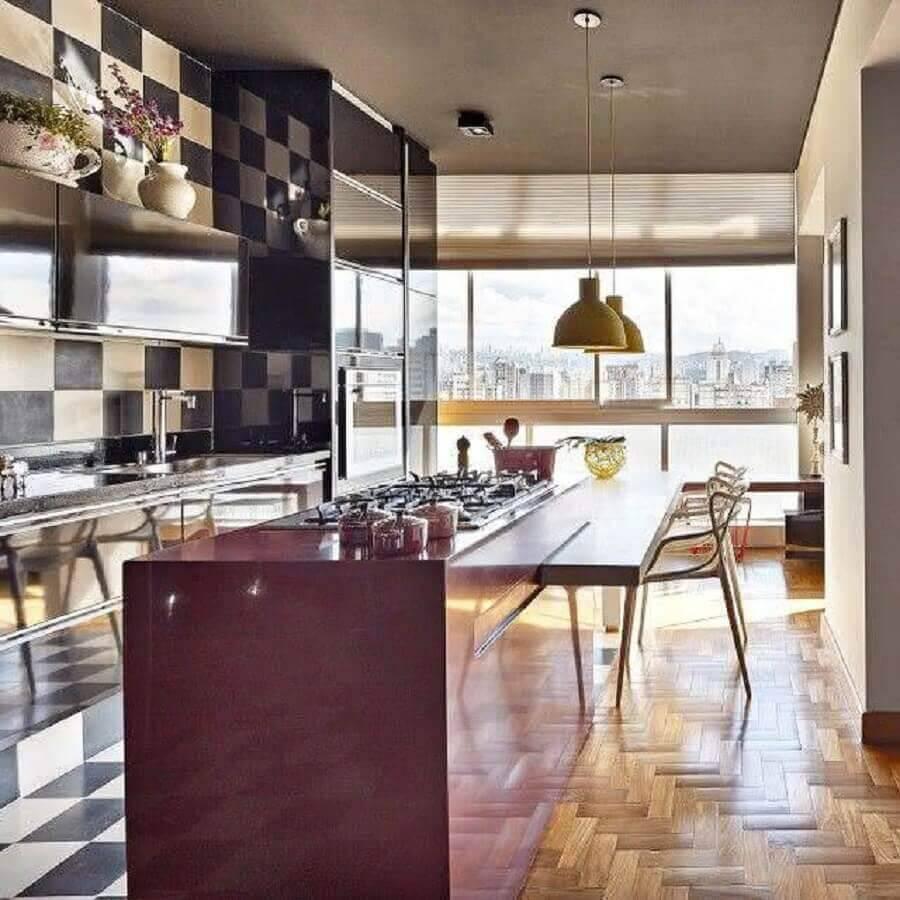 Cozinha planejada com ilha central e azulejo preto e branco.