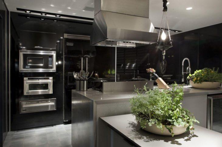 Cozinha planejada com ilha grande e armários pretos.