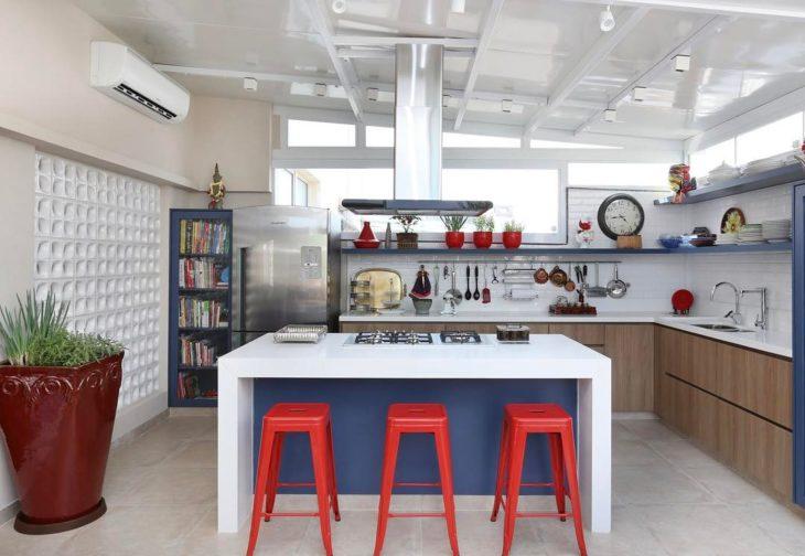 Cozinha planejada com ilha no centro e armário de madeira.