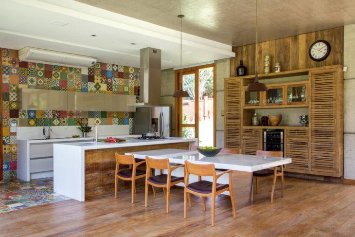 Cozinha planejada com ilha grande e decoração com azulejo colorido.