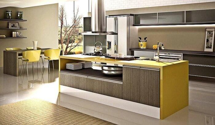 Cozinha planejada com ilha no centro e bancada amarela.