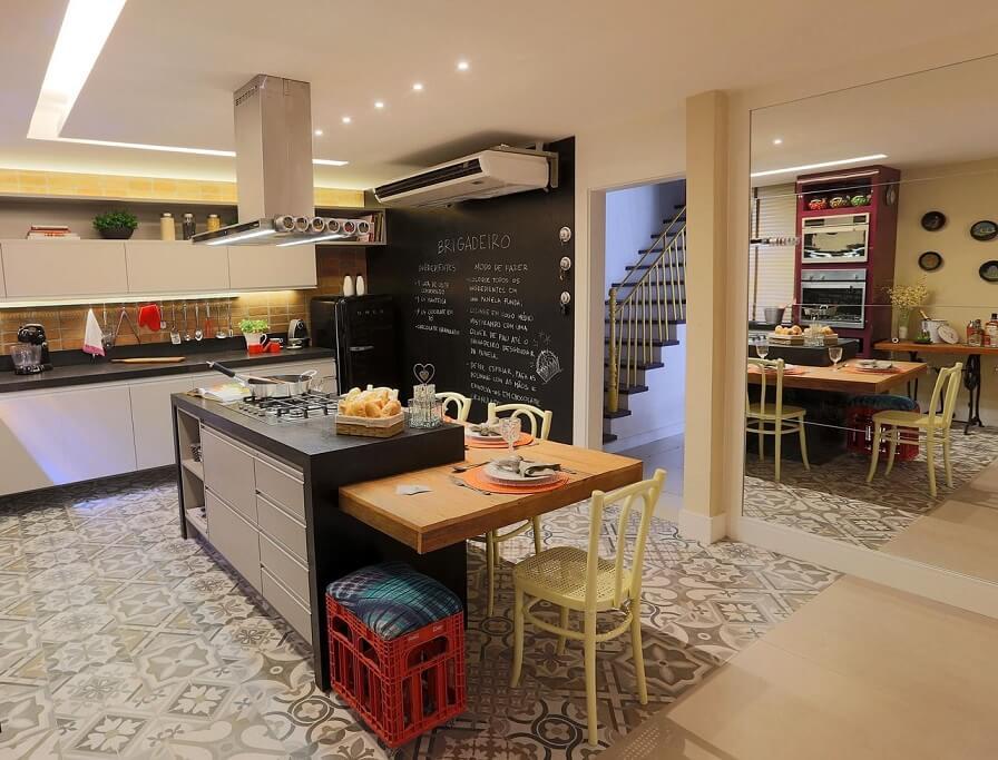 Cozinha planejada com ilha pequena e parede com tinta de lousa.