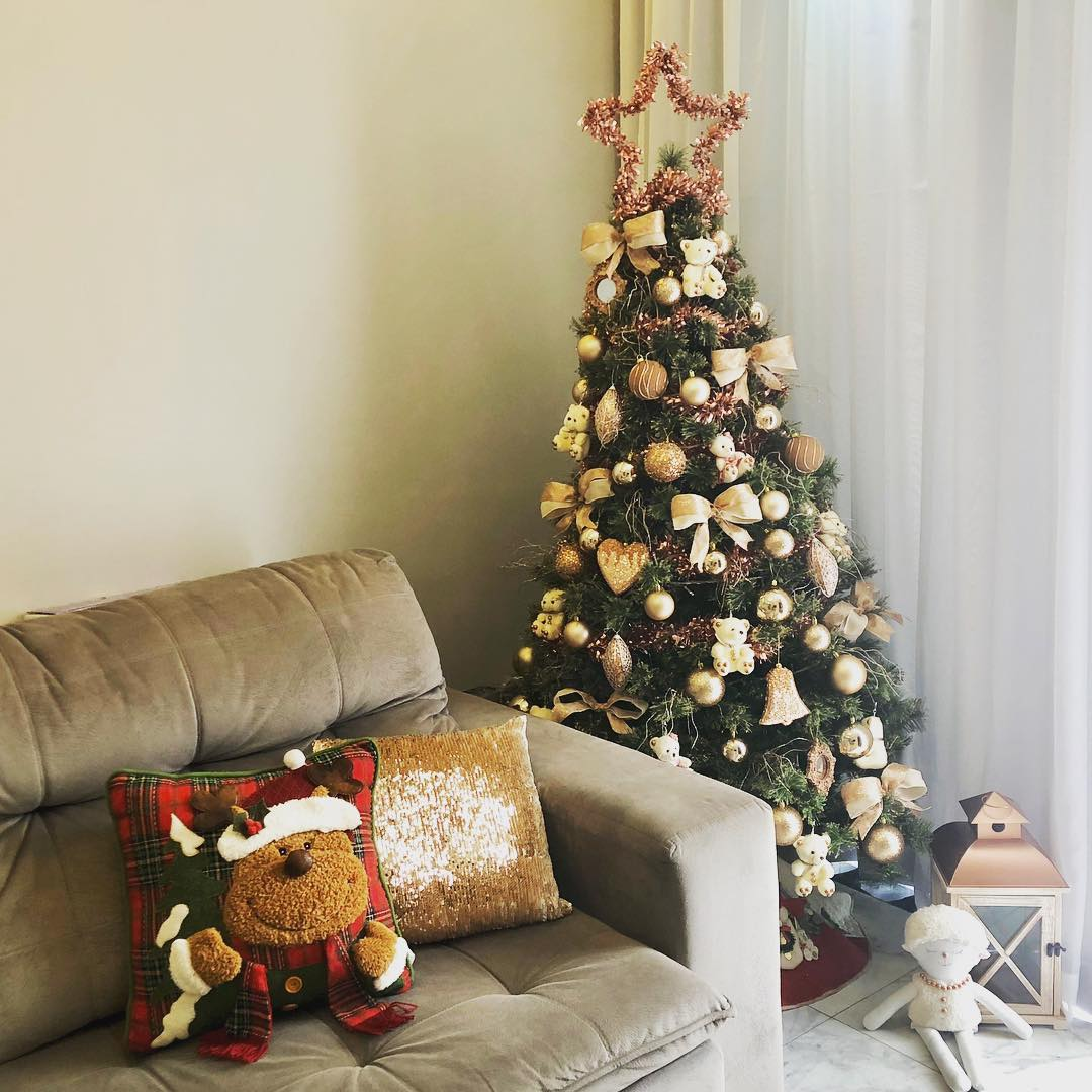 Decoração de natal para sala pequena com árvore e almofada temática.