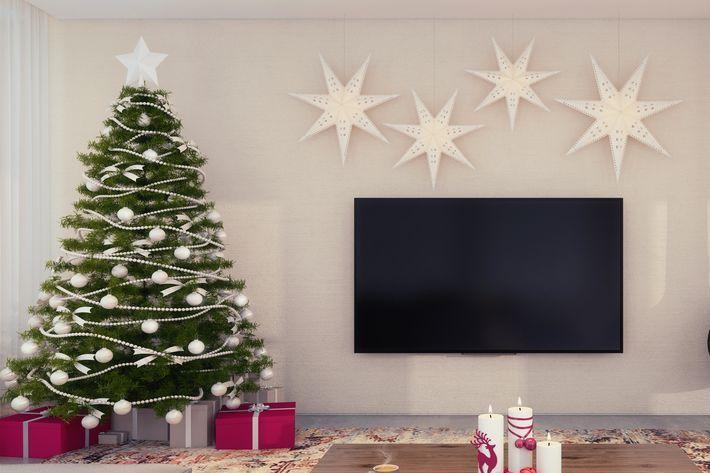 Decoração de natal para sala pequena com árvore, velas e luminária.