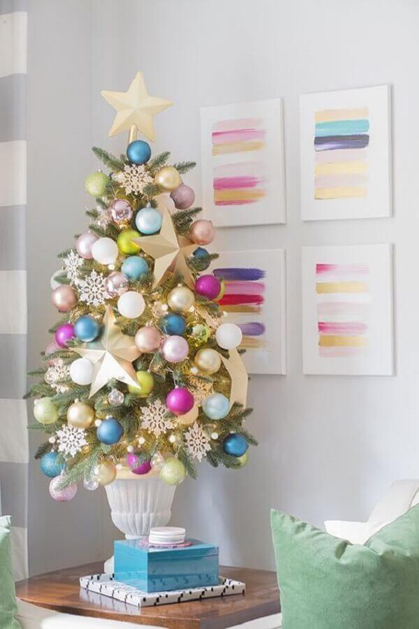 Decoração de natal para sala pequena com árvore colorida na mesa lateral.