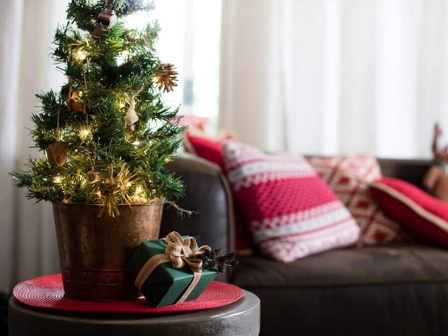 Decoração de natal para sala pequena com árvore e almofadas temáticas.