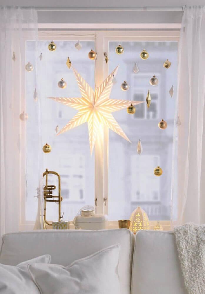 Decoração de natal para sala pequena com luminária de estrela e bolas de natal douradas.
