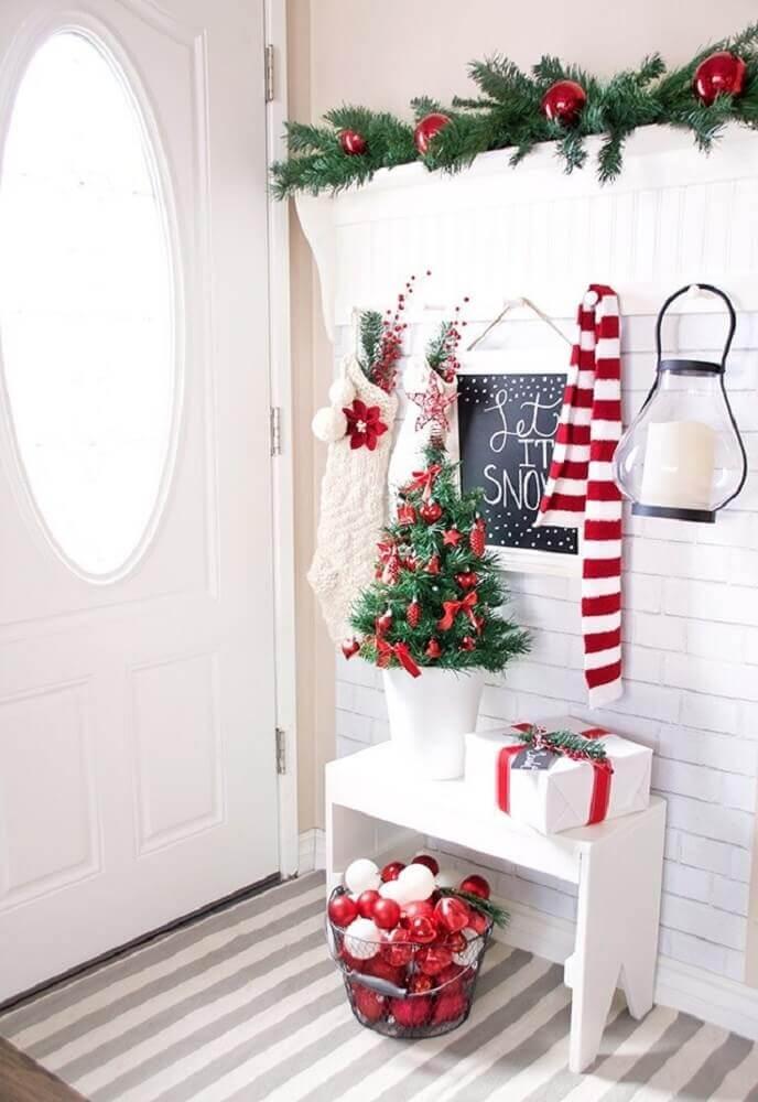 Decoração de natal para sala pequena com meias, bolas de natal e árvore.