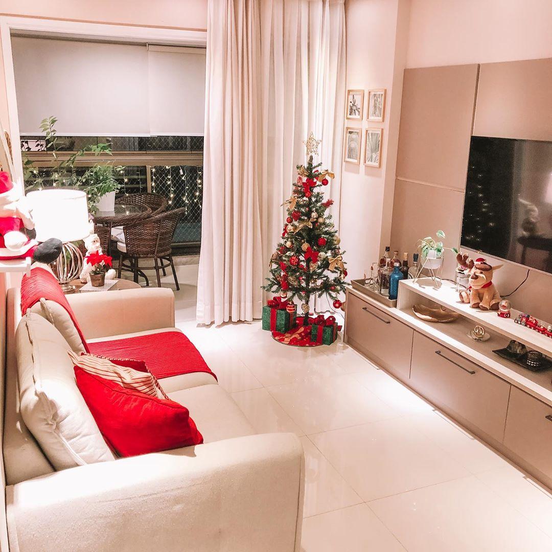 Decoração de natal para sala pequena com árvore e almofadas vermelhas.