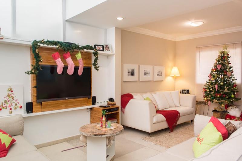 Decoração de natal para sala pequena com meias, quadros e árvore de natal.