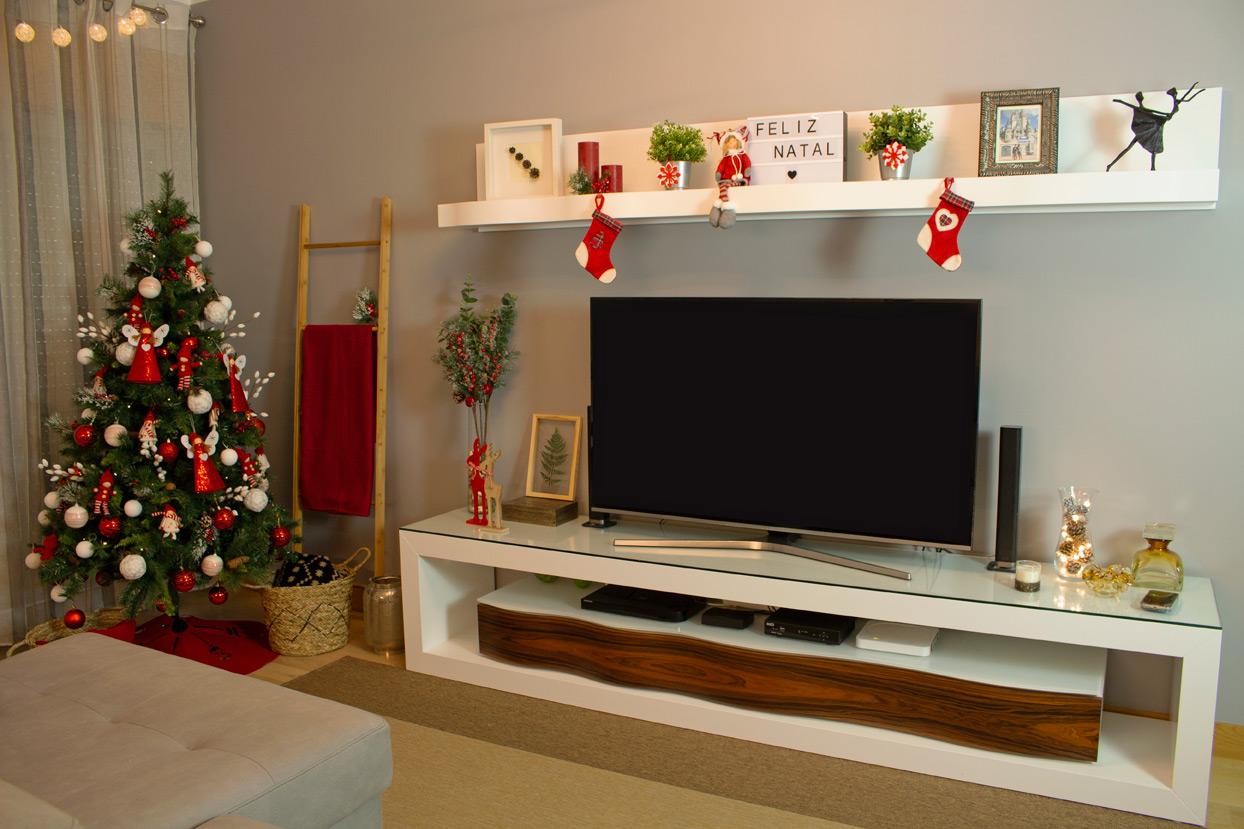 Decoração de natal para sala pequena com árvore de natal decorada, meias, velas e manta vermelha.