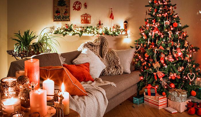 Decoração de natal para sala pequena luxuosa com árvore de natal, velas e objetos decorativos.