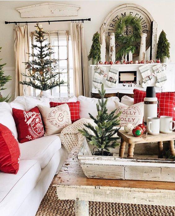 Decoração de natal para sala simples com árvores pequenas, guirlandas discretas e almofadas vermelhas.