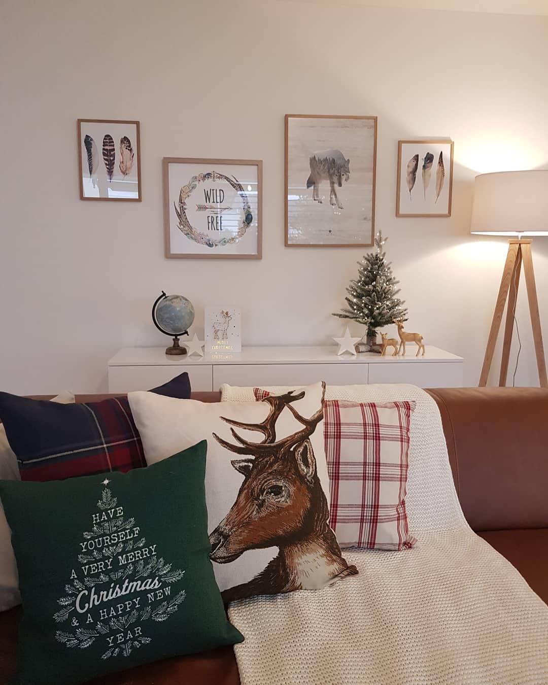 Decoração de natal para sala simples com árvore pequena, quadro, estrela e almofadas temáticas.