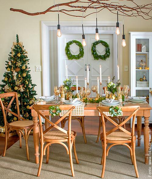 Decoração de natal para sala de jantar com cadeira decorada e taça dourada.