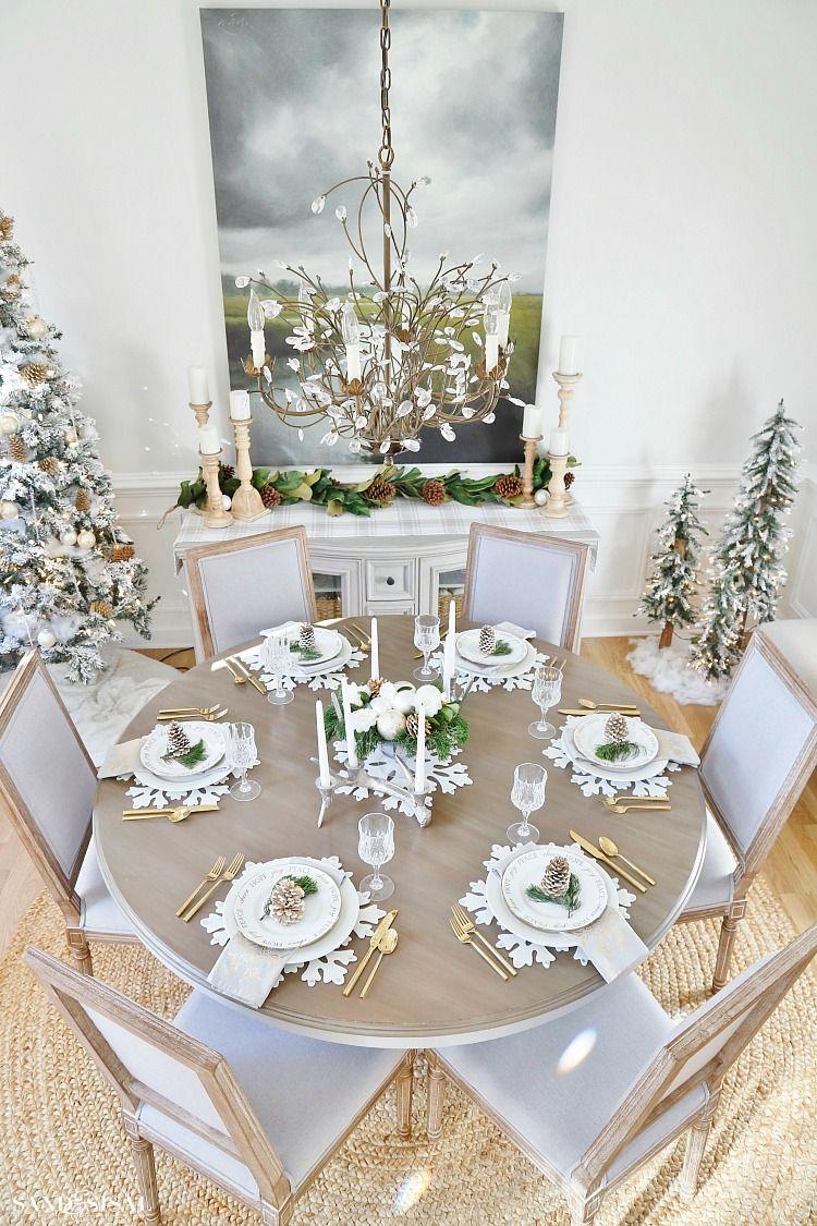 Decoração de natal para sala de jantar com árvores decoradas, talheres dourados e jogo americana temática.