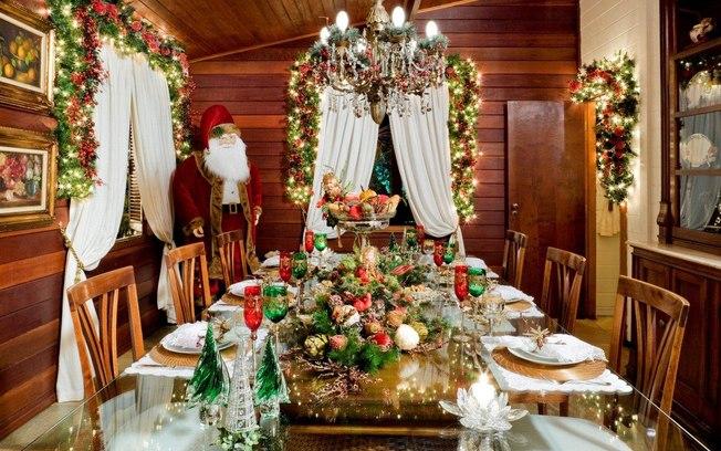 Decoração de natal para sala de jantar com arranjo de mesa e taças natalinas.