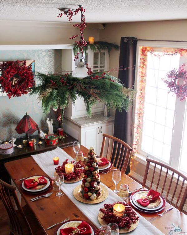 Decoração de natal para sala de jantar com árvore de bola de natal, velas, guirlandas e guardanapos.