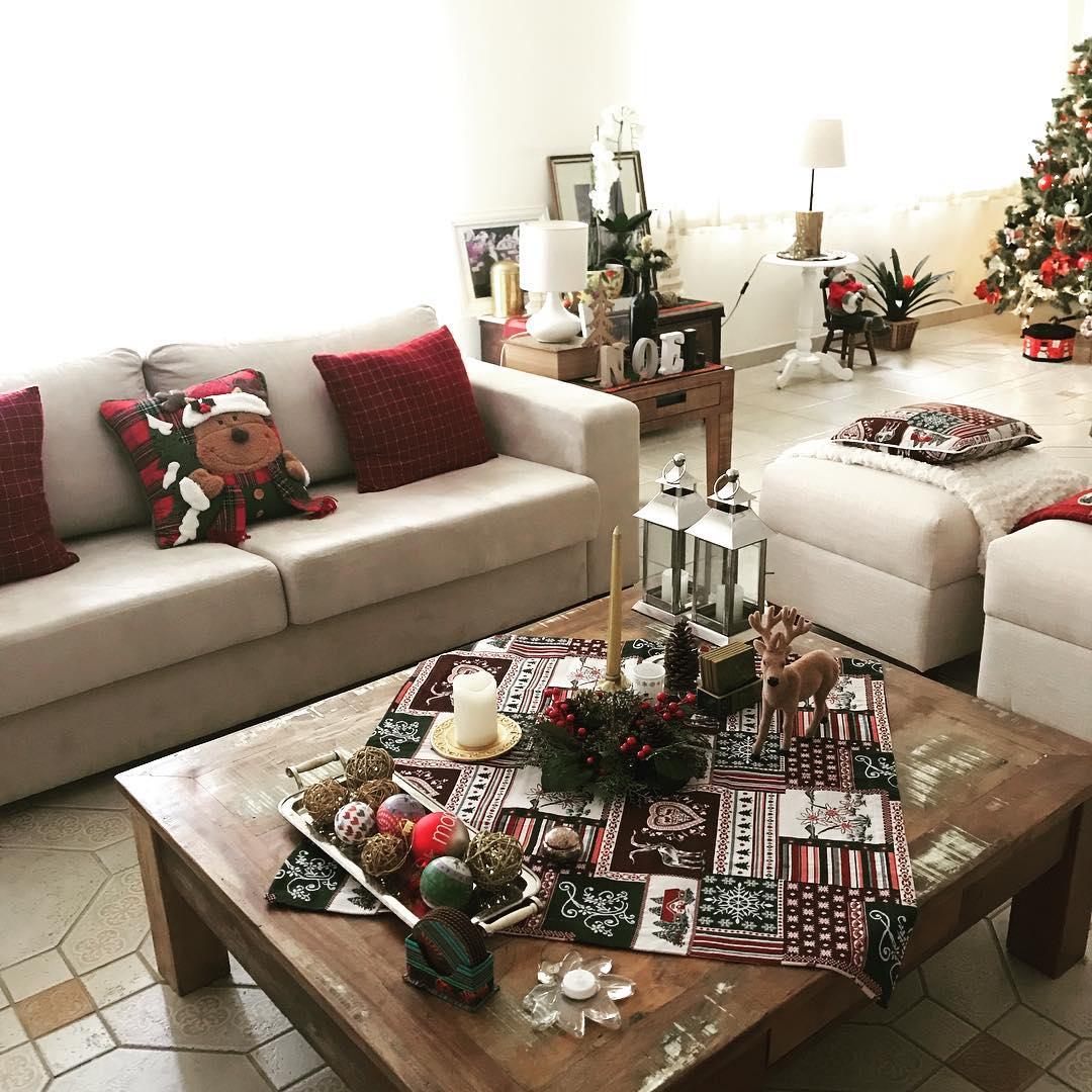 Decoração de natal para sala com arranjo decorado e almofadas temáticas.