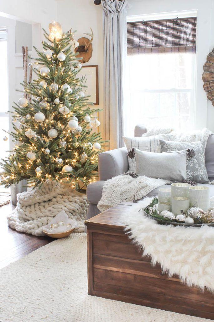Almofadas natalinas cinzas, arranjo de mesa prateado, suporte para velas brancos e manta de pelúcia.