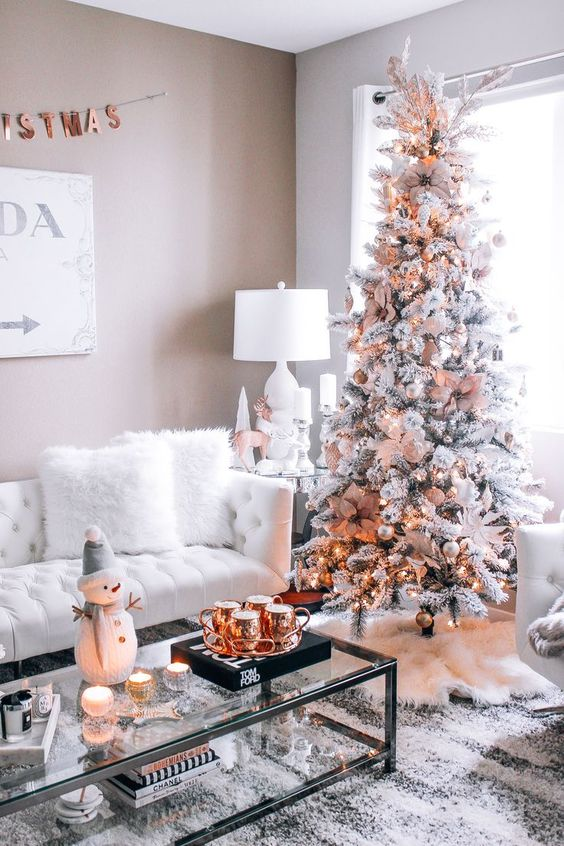 Almofada de pelúcia, velas, boneco de neve e xícaras em bronze.