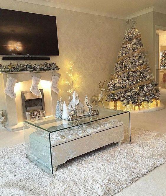 Ambiente decorado com lareira iluminada, presentes iluminados e árvore com pisca pisca.