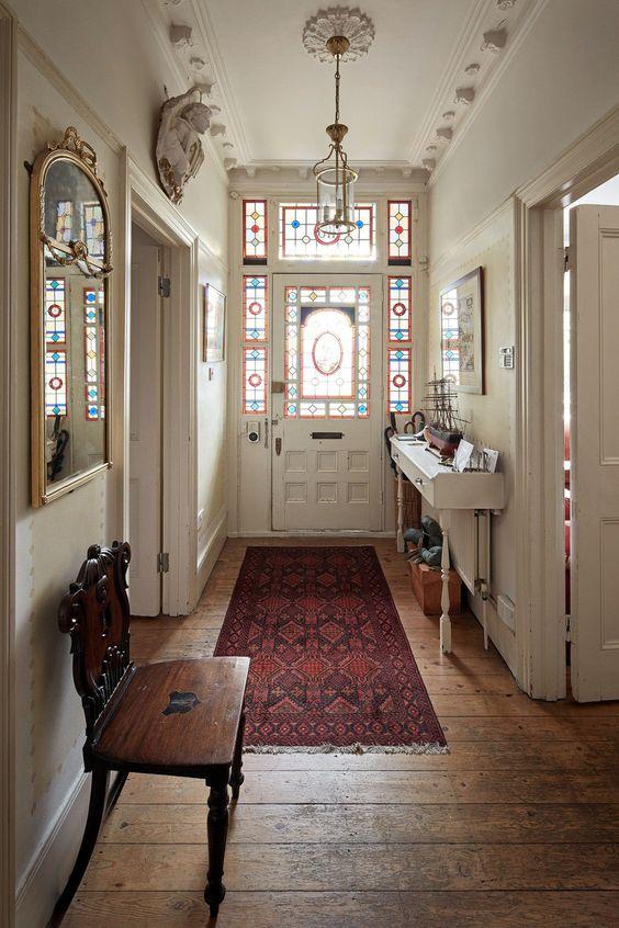 hall de entrada com vitral e tapete persa