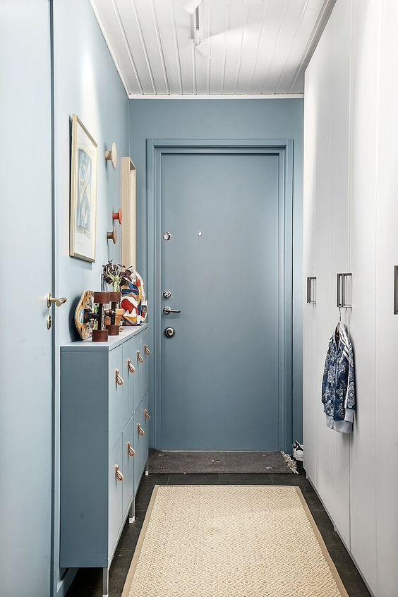 hall de entrada azul com armário decorado