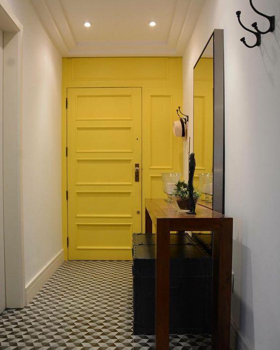 porta e parede amarela com boiserie