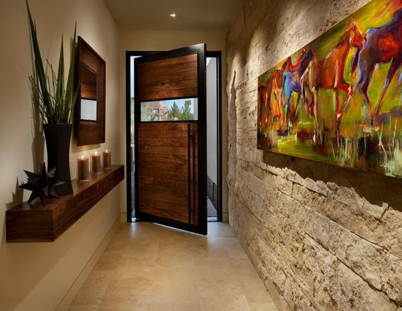 Hall de entrada com parede de pedra e porta pivotante