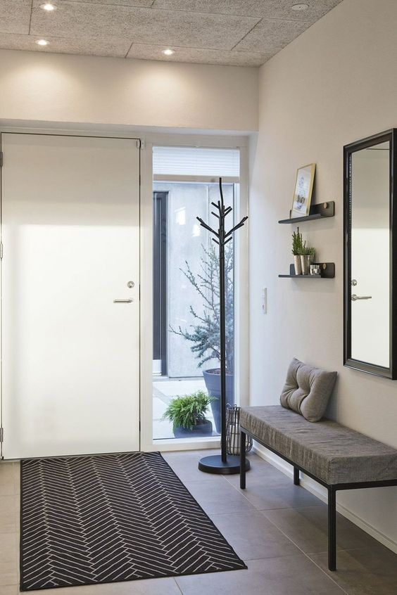 hall de entrada moderno com estofado e espelho simples