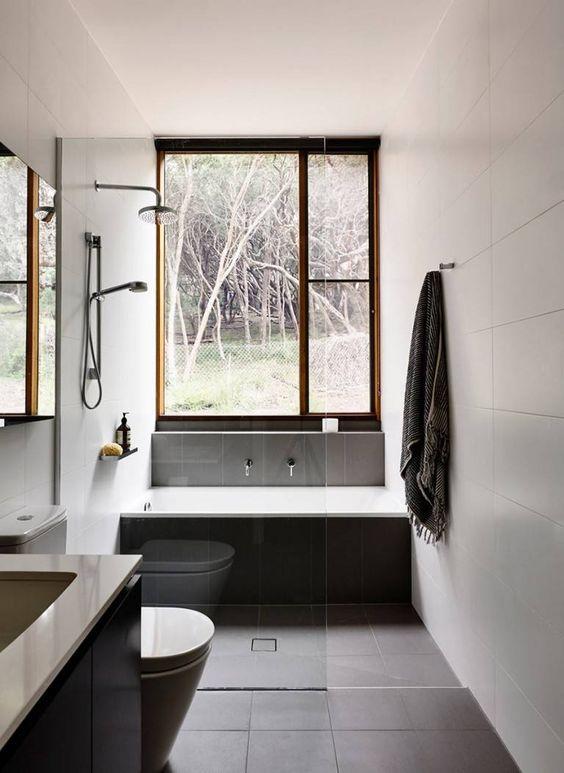 banheiro com banheira e chuveiro cinza