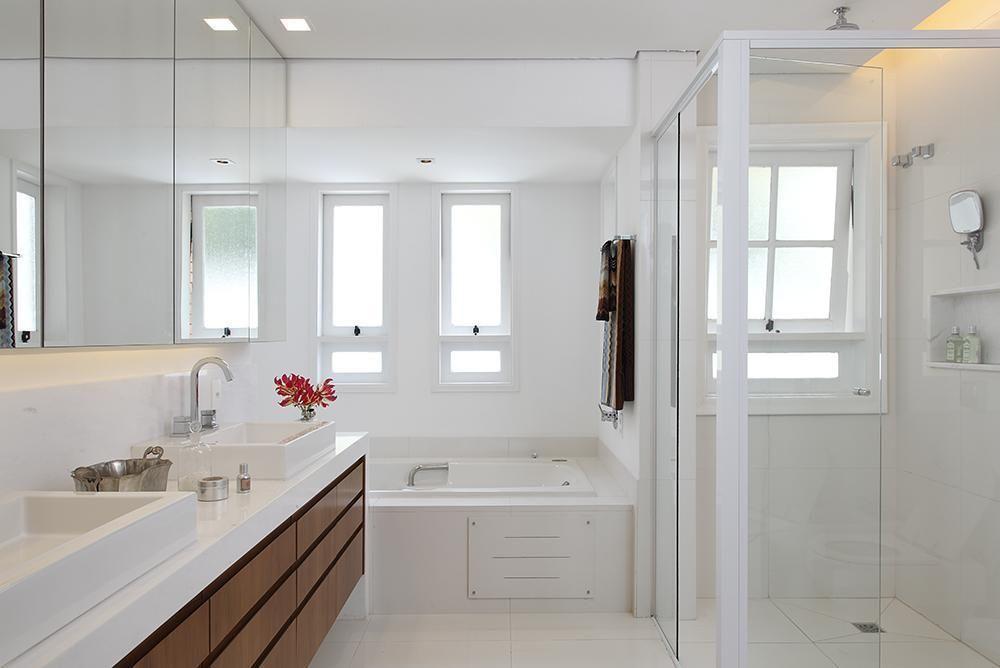 Decoração clean com banheira e box grande.