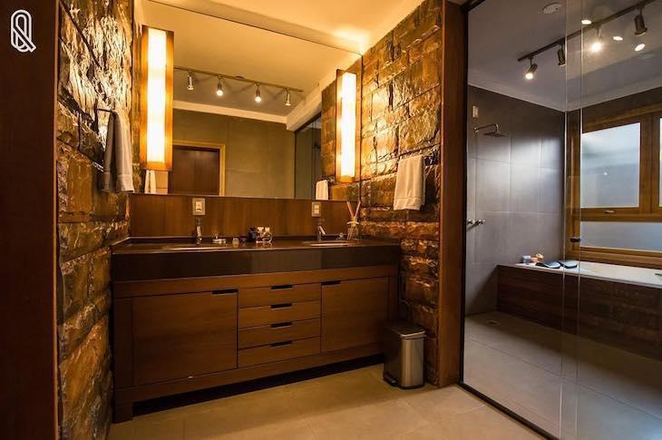 Decoração luxuosa com banheira, trilho de luz e luminária no espelho.