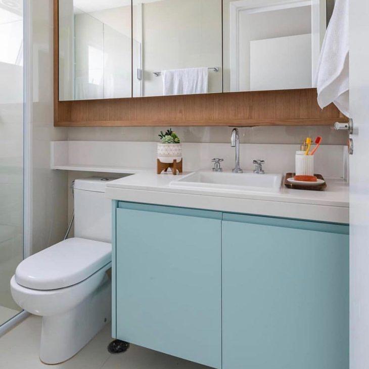 Modelos de banheiro simples com armário azul e bancada de granito.