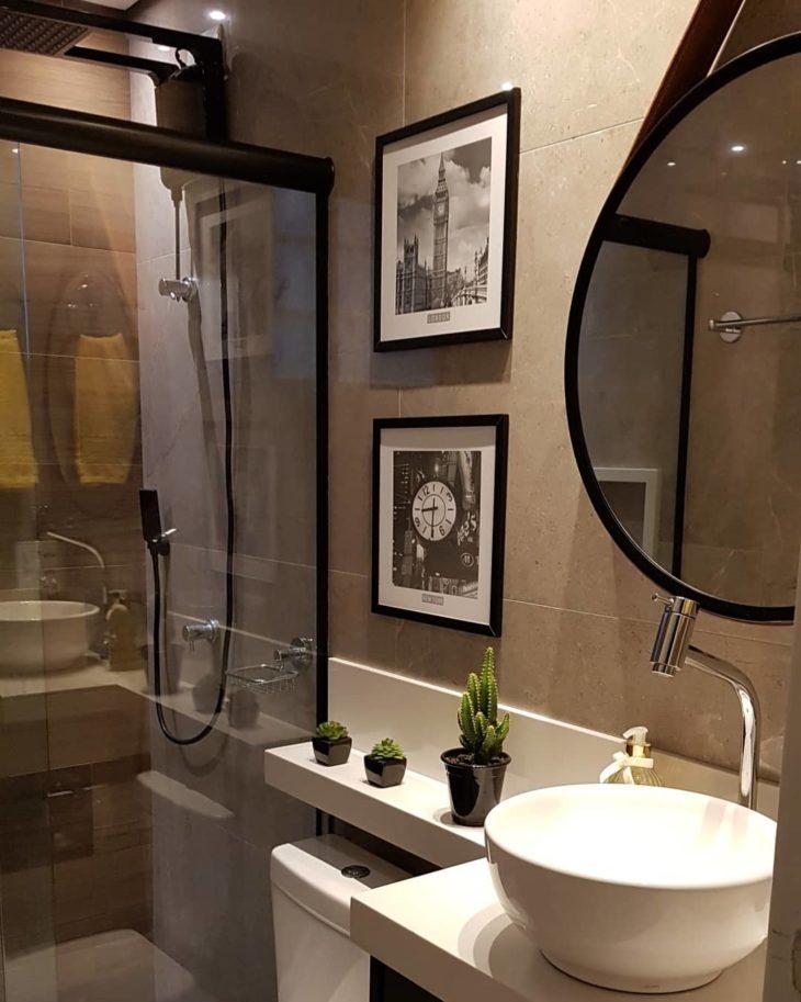 Modelos de banheiro moderno  com revestimento cinza e quadros decorativos.