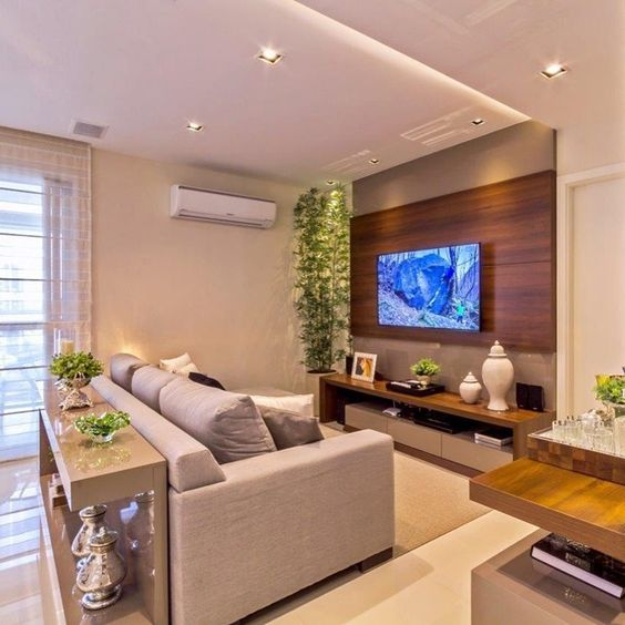 Sala decorada com sofá cinza e painel de madeira.