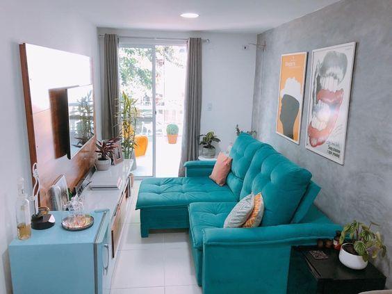 Sala pequena com sofá, raque e frigobar azuis.