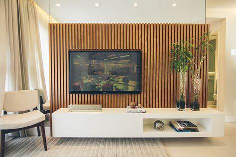 Sala planejada com espelho ao redor do painel de madeira.