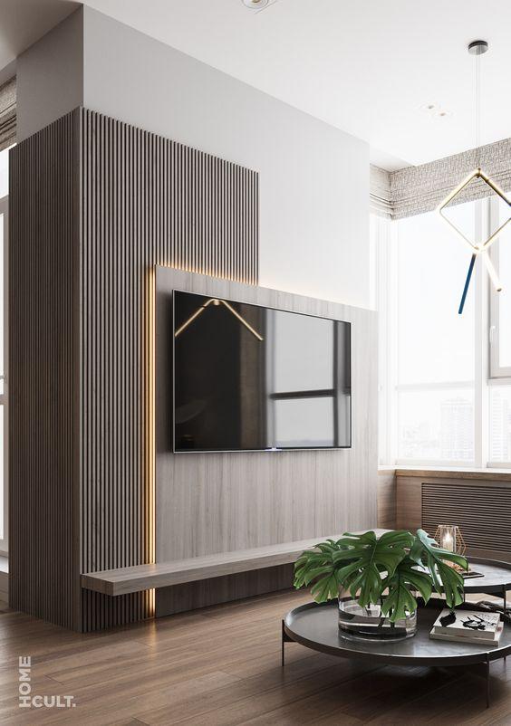 Sala planejada com painel de tv de madeira e mesas de centro redondas.