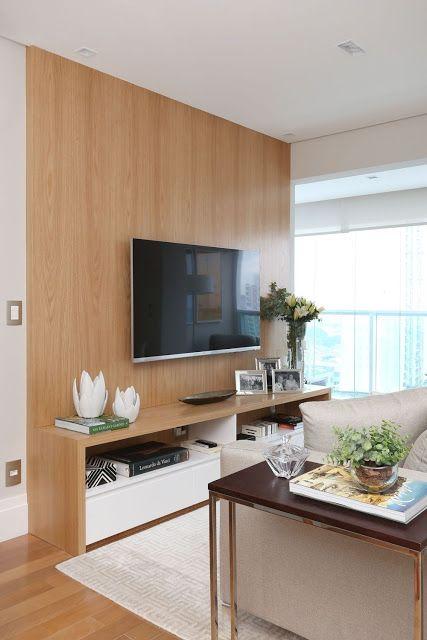 Sala pequena com painel de tv de madeira com uma prateleira para artigos decorativos.