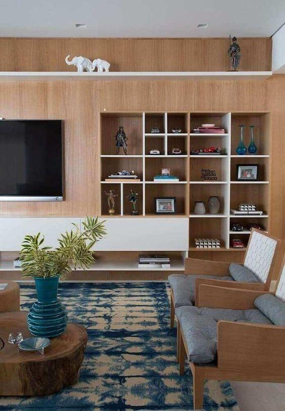 Sala decorada com tons amadeirados, azul e cinza.