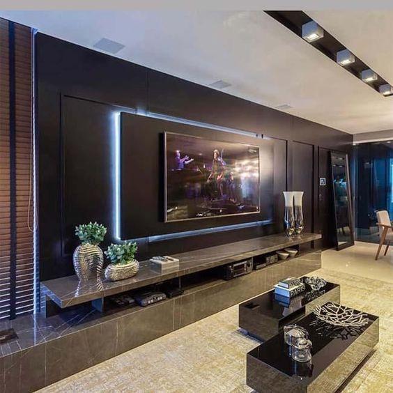 Sala planejada com parede inteira preta com duas mesas de centro.
