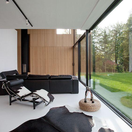 Sala com móveis pretos e parede de vidro.