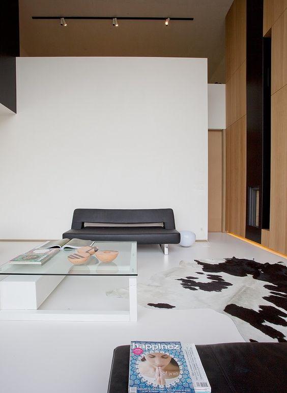 Sala branca com tapete de couro preto e branco e mesa de centro de vidro.