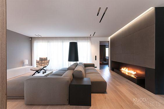 Ampla sala moderna com dois sofás, uma poltrona e lareira.