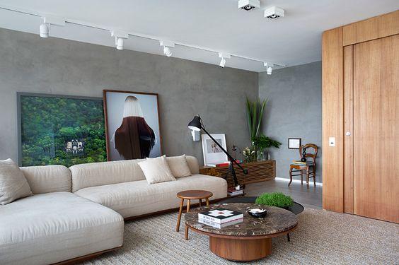 Sala planejada com paredes cinzas e sofá claro.