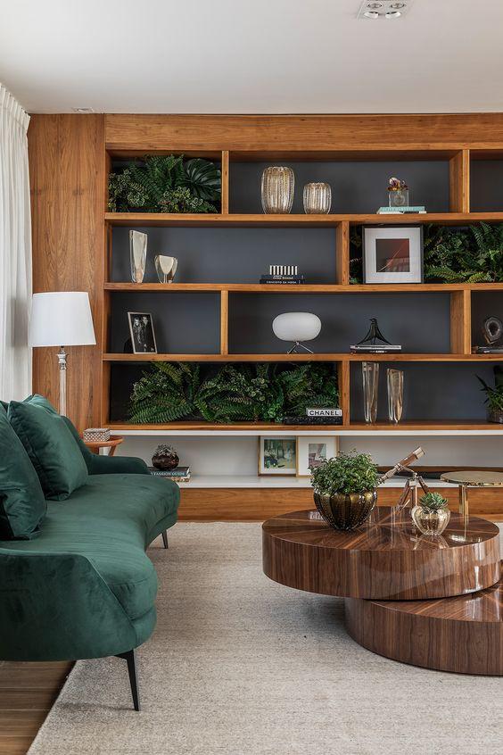 Sala planejada com sofá verde e mesa de centro de madeira.