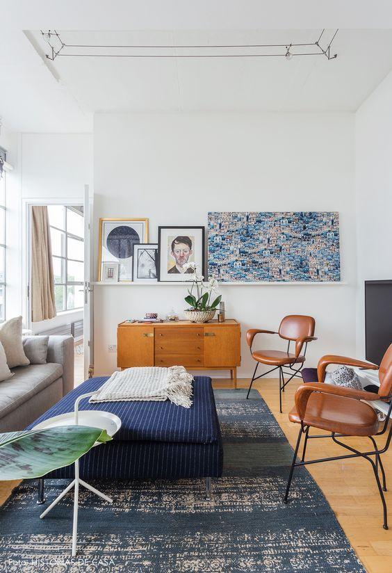 Sala de estar com sofá cinza, cadeiras de couro marrons e armário de madeira.